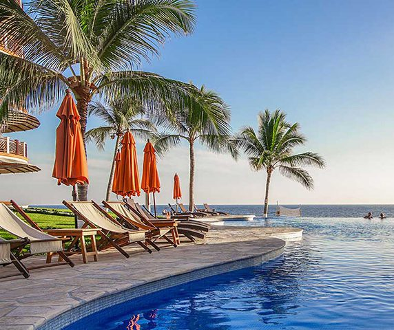 Chairs and umbrellas beside the infinity pool at Vivo Resorts in Puerto Escondido MX