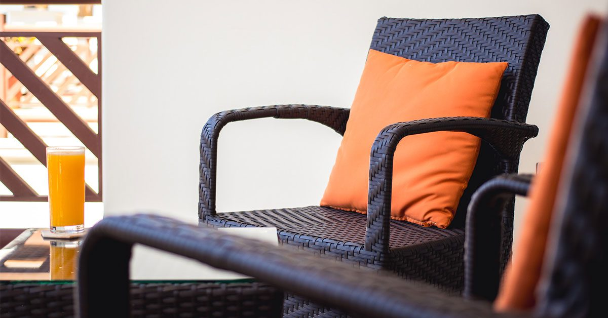 Balcony with wicker chairs and a drink on a wicker side table
