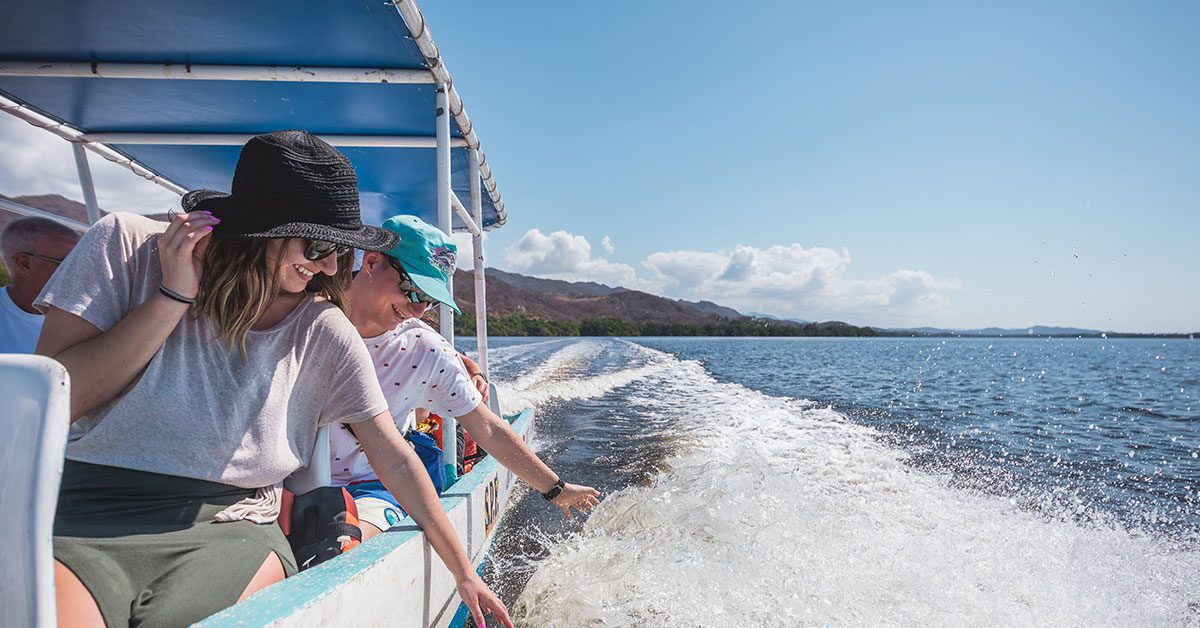 Couple touching the water from a tour boat on Laguna in Puerto Escondido